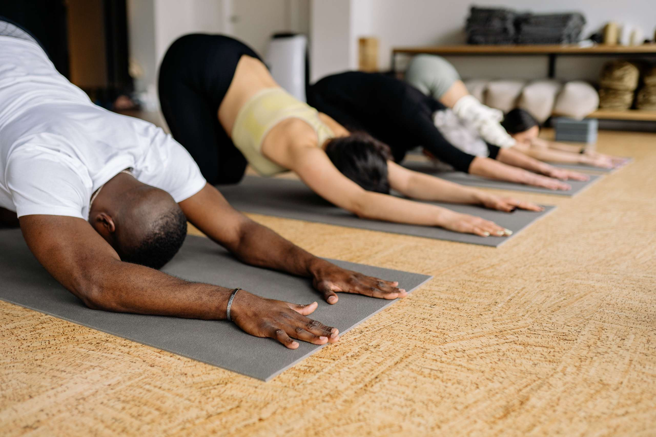 Photo of men and women performing a yoga exercise